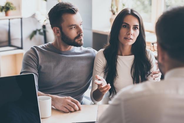 Probleme mit psychologen teilen. selbstbewusstes junges paar, das dem psychologen seine probleme erzählt, während es zusammen am schreibtisch sitzt