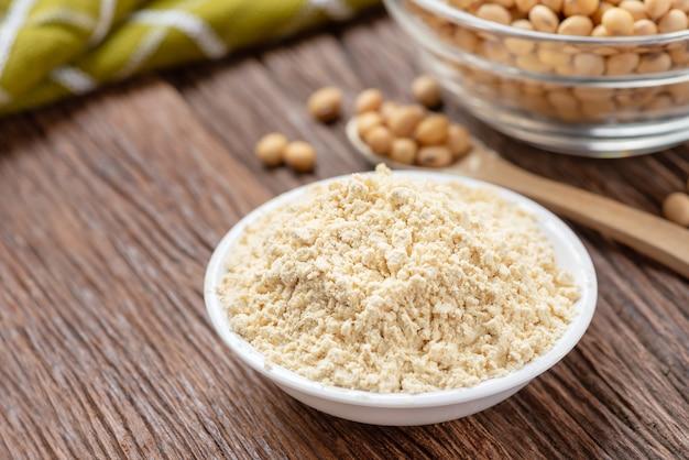 Produkt des sojamehls in der schüssel mit sojabohne, kinakomehl.
