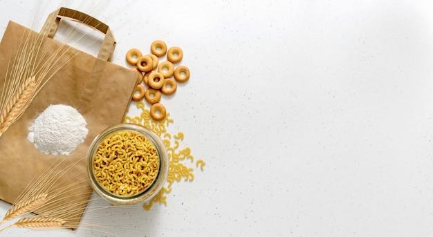 Produkte aus weizenmehl. weißmehl, weizenähren und rohe nudeln in schüssel auf papierverpackung.