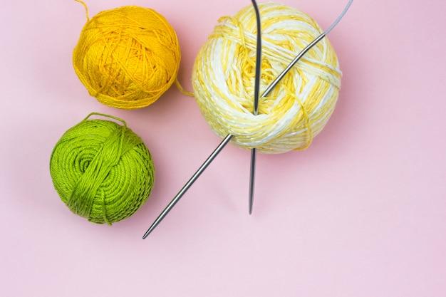 Produkte für handarbeiten, stricken. bälle aus gelbem, grünem, lila garn, stricknadeln