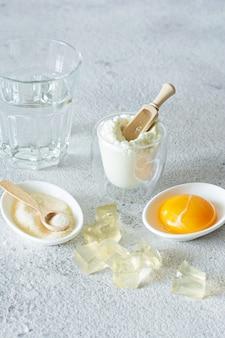 Produkte (kollagenpulver, gelatine, eigelb), die kollagen enthalten. gelatinewürfel. kollagenpulver auf hellem hintergrund. zusätzliche proteinaufnahme. natürliche schönheits- und gesundheitsergänzung für haut, knochen, gelenke