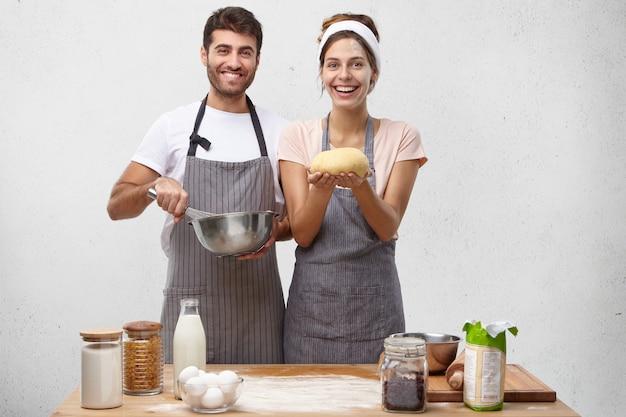 Produkte, lebensmittel, küche und kochkonzept. porträt des glücklichen positiven jungen europäischen paares, das hausgemachtes brot backt