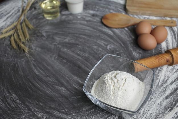 Produkte und werkzeuge zum backen von brot oder kuchen auf einem grauen tisch in streumehl