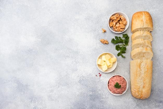 Produkte zum kochen eines sandwiches. hühnerpastete und butter, nüsse und petersilie.
