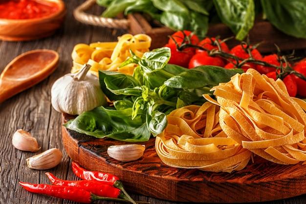 Produkte zum kochen - nudeln, tomaten, knoblauch, pfeffer und basilikum.