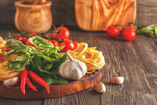 Produkte zum kochen von nudeln, tomaten, knoblauch, pfeffer und basilikum auf dem alten hölzernen hintergrund