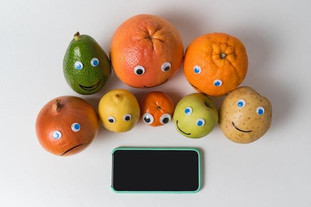 Produktfiguren mit lustigen gesichtern und smartphone mit schwarzem bildschirm. anwendung zur gewichtsreduktion, konzept