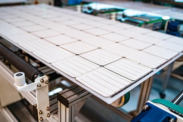 Produktion von sonnenkollektoren, mann arbeitet in der fabrik. nahaufnahme von spezialmaschinen in der fabrik für solarmodule