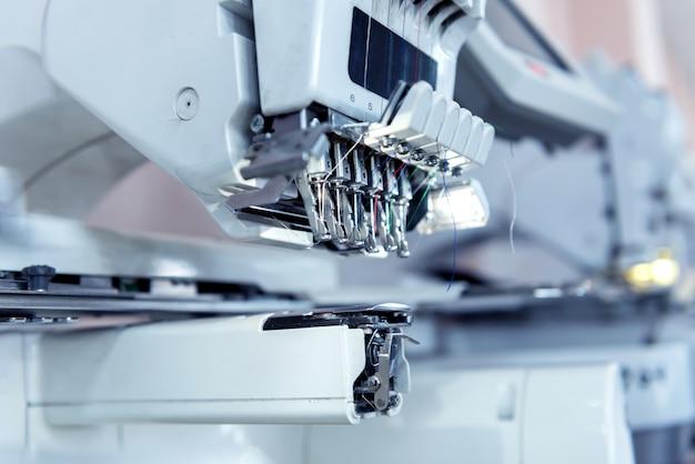 Produktionslinie der textilindustrie. textilfabrik. arbeit schneiderei stoff. professionelle stickmaschine. moderne ausrüstung