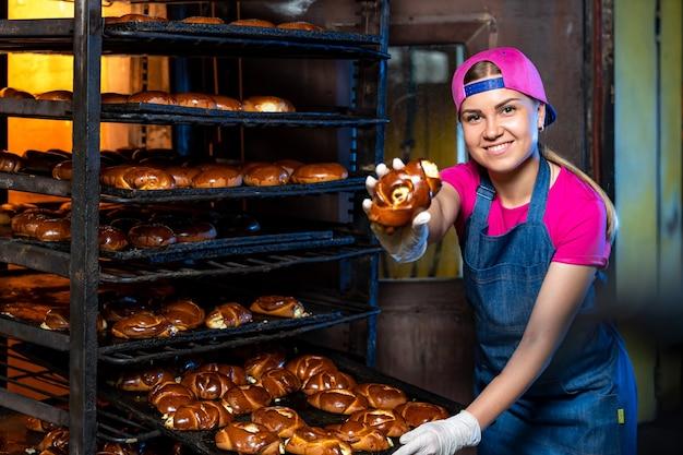 Produktionslinie zum backen von keksen. regale mit gebäck. frau mit tablett in der fabrik. nahaufnahme.