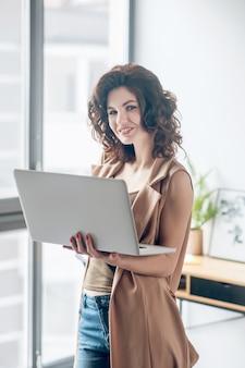 Produktiv sein. dunkelhaarige hübsche frau, die an einem laptop arbeitet und zufrieden aussieht