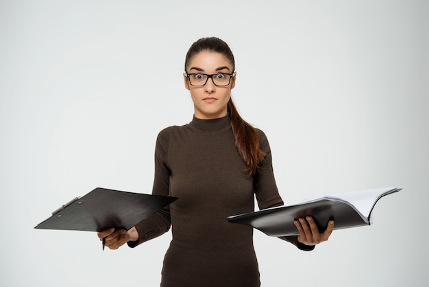 Produktive kluge geschäftsfrau, die bericht studiert, dokumente hält