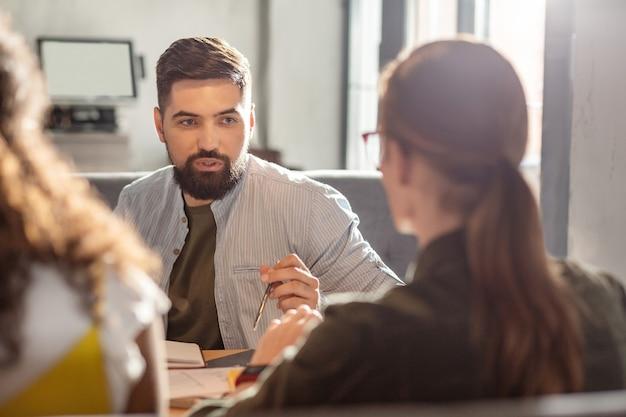 Produktive zusammenarbeit. angenehmer bärtiger mann, der seinen kollegen anschaut, während er die idee für ein startup diskutiert