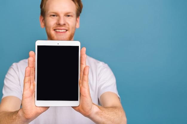 Produktpräsentation. beförderung. junger mann, der in den händen tablet-computer mit leerem bildschirm hält