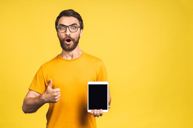 Produktpräsentation. förderung. junger bärtiger mann, der in den händen tablet-computer mit leerem bildschirm hält. getrennt über gelbem hintergrund.