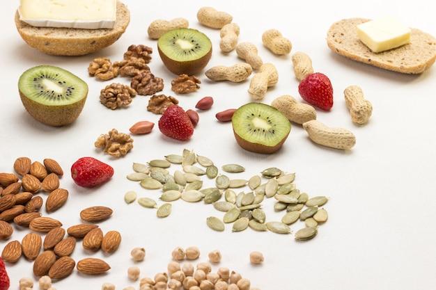 Produktset für ein ausgewogenes frühstück: mandeln, kürbiskerne, erdbeeren, kiwi