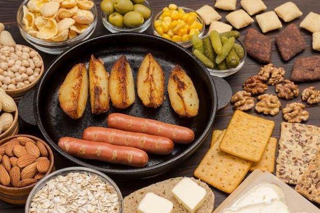 Produktset für ein ausgewogenes frühstück: würstchen kartoffeln, nüsse, früchte, kekse butter.