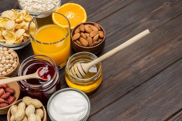 Produktset zum frühstück: orange, saft, joghurt, marmelade, haferflocken.