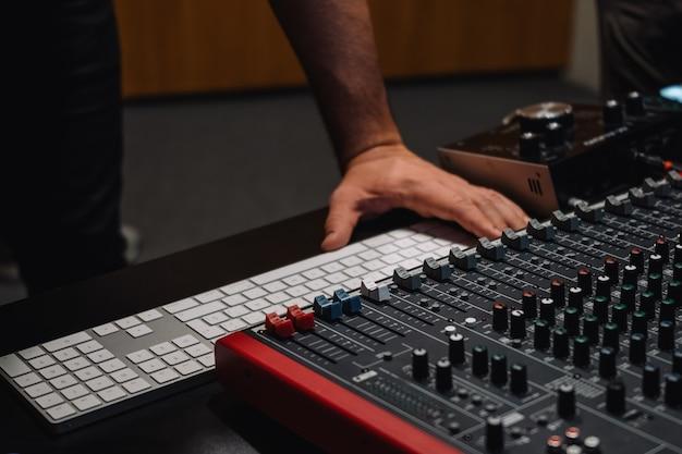 Produzentenhände an der tastatur in einem studiomusiker, der musik in heimstudio-musikproduktionsgeräten arrangiert und mischt