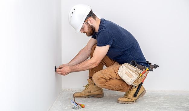 Professionell in overalls mit einem elektrikerwerkzeug an der weißen wand. hausreparatur- und elektroinstallationskonzept.