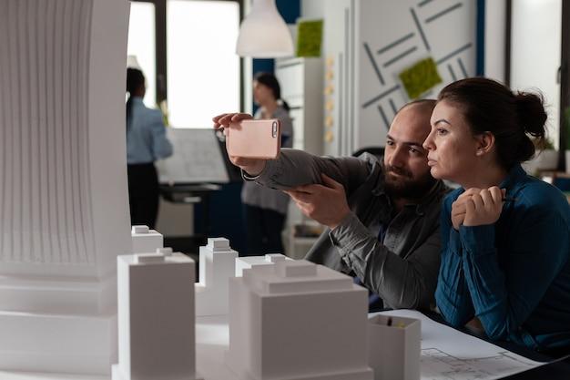 Professionelle architektenkollegen arbeiten am smartphone, das am schreibtisch sitzt, während sie das gebäudemodell maquette betrachten. ingenieure, die über ein projekt in der bauindustrie sprechen