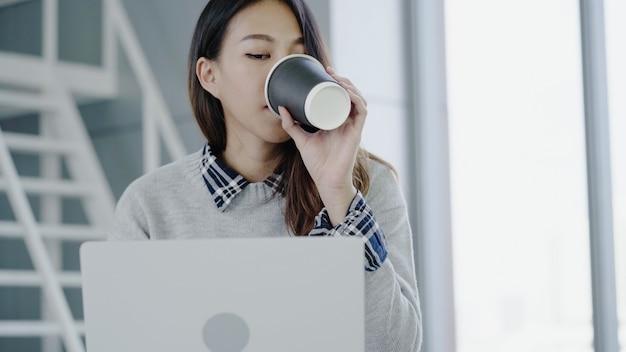 Professionelle asiatische geschäftsfrau, die in ihrem büro über laptop arbeitet.
