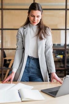 Professionelle attraktive geschäftsfrau, die laptop im büro betrachtet