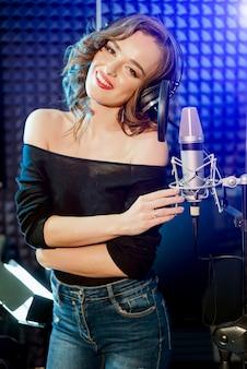 Professionelle aufnahme des songs im studio. schöne frau in den kopfhörern nahe dem mikrofon. mädchen auf dunklem aufnahmestudio. porträt. nahansicht.