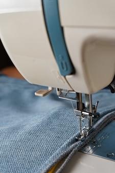 Professionelle ausrüstung. moderne nähmaschine mit spezialdruckfuß. der prozess des nähens einer dekorativen kantenschnur aus blauem kleidungsstück.