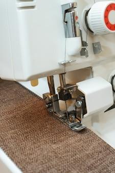 Professionelle ausrüstung. moderner overlock-nähmaschinendruckfuß zur verwendung mit kleidungsstücken. nahaufnahmefoto.