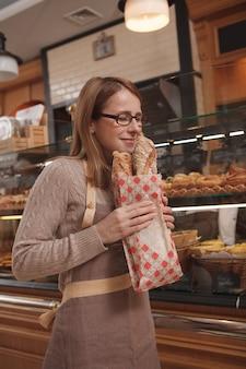 Professionelle bäckerin, die köstliches frisch gebackenes brot riecht und in ihrem bäckereigeschäft arbeitet