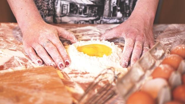 Professionelle bäckerin, die teig mit eiern und mehl zum osterbacken kocht
