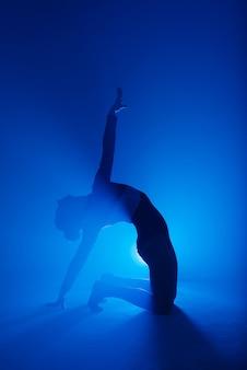 Professionelle ballerina tanzt ballett in einem rauch. frau im schwarzen body auf flutlichthintergrund.