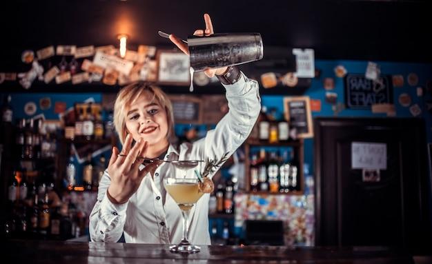 Professionelle barkeeperin demonstriert den prozess der zubereitung eines cocktails im nachtclub