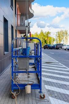 Professionelle bauwiege oder gondel für bauarbeiten in der höhe und fensterreinigung eines hochhauses. industrieausrüstung für arbeiten in der höhe.