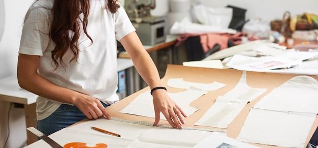 Professionelle designerin, die papiermuster mit maßband, lineal und kurve herstellt