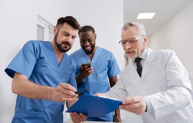 Professionelle details besprechen. konzentrierter lächelnder senior mentor, der im krankenhaus arbeitet und den täglichen bericht überprüft, während er sich mit praktikanten unterhält