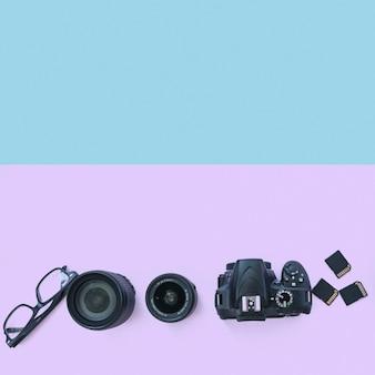 Professionelle digitalkamera mit zubehör und schauspiel auf doppelhintergrund
