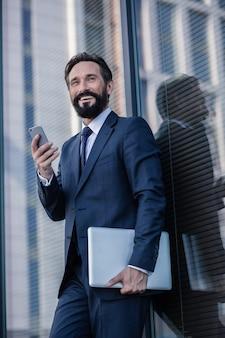 Professionelle einstellung. handsoem lächelnder geschäftsmann, der einen laptop und ein smartphone hält, während er sich an die wand lehnt