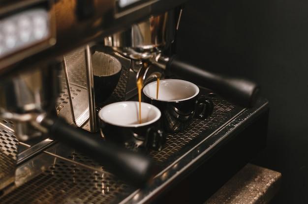 Professionelle espressomaschine, die frischen kaffee in eine keramikschale gießt.