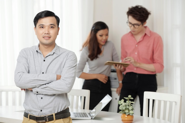 Professionelle ethnische arbeitskraft mit kollegen im büro