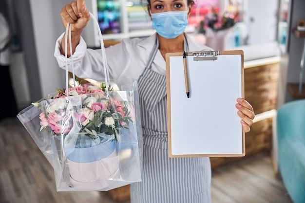 Professionelle floristin, die einen blumenstrauß und leeres papier zeigt