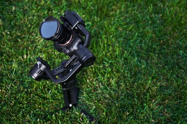 Professionelle foto- und videokamera-nahaufnahme auf einem hintergrund des grünen grases