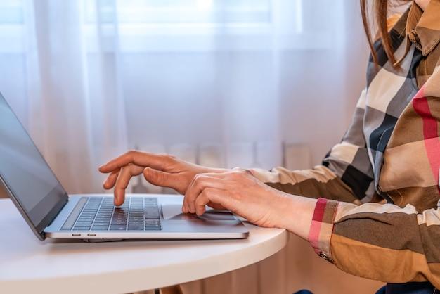 Professionelle frau, die durch das bürofenster sitzt, bedient einen laptop