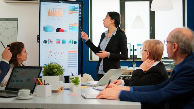 Professionelle führungskraft beim briefing ihrer kollegen, erläuterung der unternehmensstrategie während des brainstormings. multiethnische geschäftsleute, die während der konferenz in einem professionellen startup-finanzbüro arbeiten