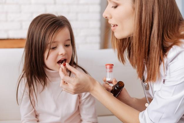 Professionelle fürsorgliche krankenschwester, die einem kleinen mädchen tabletten gibt, während sie dabei hilft, sich zu erholen und mit ihren gesunden trinkgeldern zu teilen
