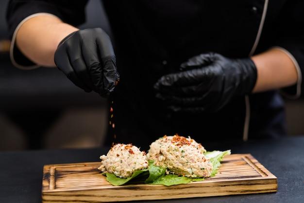 Professionelle gastronomie. koch in schwarzen kochhandschuhen, die thunfischsalat auf rustikalem holzbrett würzen.