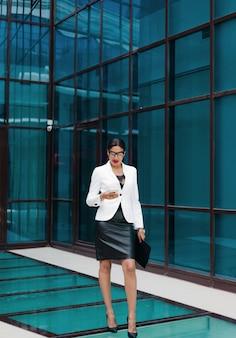Professionelle geschäfts-afro-frau in eleganter weißer jacke und rock mit ordner mit dokumenten in ihren händen verwenden smartphone