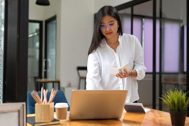 Professionelle geschäftsfrau, die an ihrem projekt arbeitet, während sie notizbuch hält und auf laptop schreibt