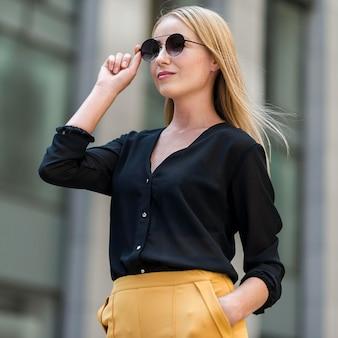 Professionelle geschäftsfrau, die im anzug und in der sonnenbrille draußen aufwirft